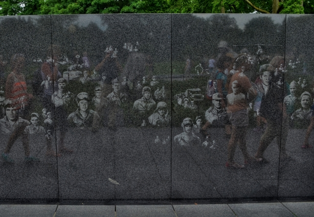 Visitors to the Korean War Memorial pass a wall etched with candid photos of G.I.s from the conflict.