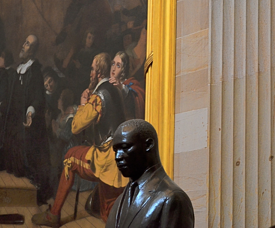 A somber bronze bust of Dr. King in the U.S. Capitol rotunda, flanked by the painting The Embarkation Of The Pilgrims. 1/30 sec., f/5.6, ISO 640, 55mm.