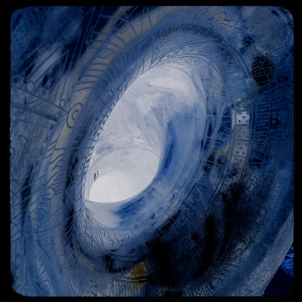 The bell of an engraved sousaphone, converted into a negative and color-boosted to resemble a faux vortex.