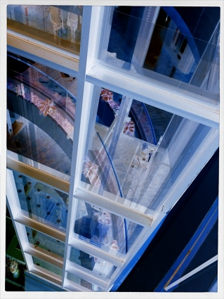 A glass elevator at a shopping mall, converted to a negative, then a fake Technicolor filter in a matters of seconds, via phone app.