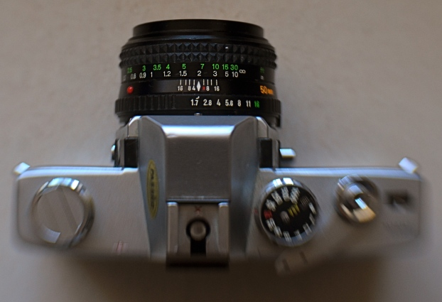 My antedeluvian Minolta SRT-500 camera body, crowned by its original f/1.7 50mm prime kit lens. Guess which one is worth its weight in gold?