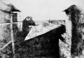 1820's view from the upper floor of Nicéphore Niépce's house is generally acknowledged as the first true photograph, revealing details of a distant pear tree, a slanted barn roof, and the secondary wing of the house (at right).
